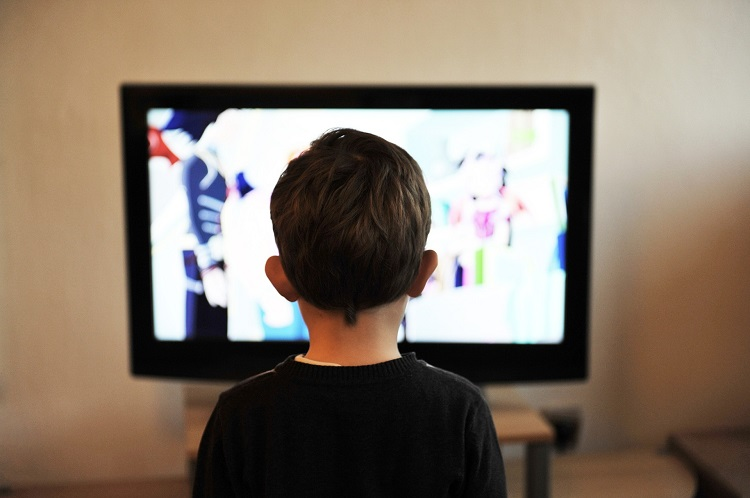 Child standing in front of a large TV